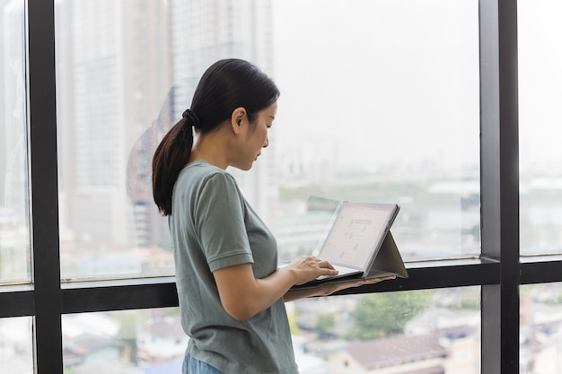Kobieta stojąca przy oknie trzymająca laptopa