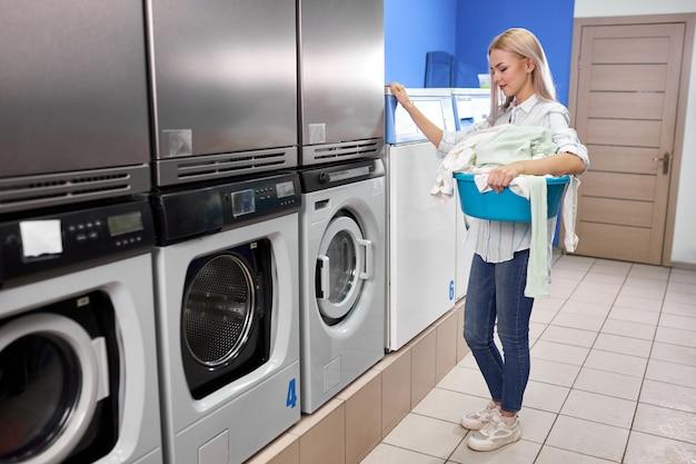 Kobieta stojąca sama z brudnymi ubraniami w samoobsługowej pralni z suszarkami. kobieta w casual stoi trzymając umywalkę z ubraniami.