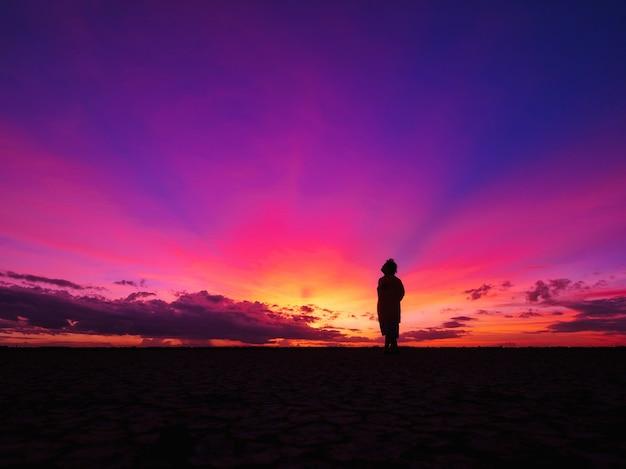 Kobieta stojąca samotnie na polu twarzą do słońca podczas pięknego zachodu słońca.