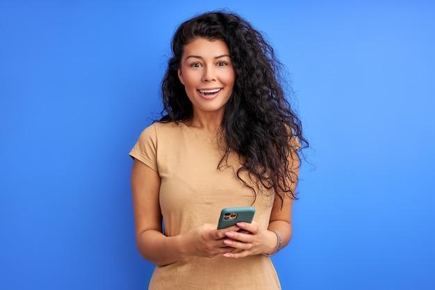 Kobieta stojąca śmiejąc się trzymając telefon komórkowy w rękach, jest zaskoczona wiadomościami, szczęśliwa