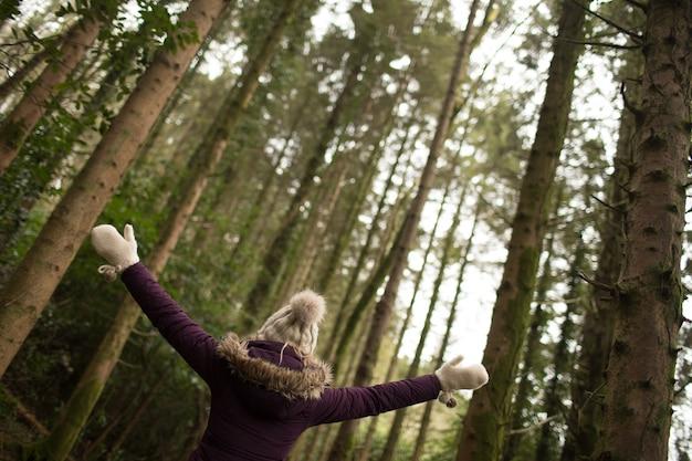 Kobieta stojąca w lesie z szeroko otwartymi ramionami