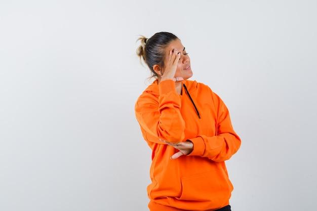 Kobieta stojąca w myślącej pozie w pomarańczowej bluzie z kapturem i wyglądająca na marzycielską