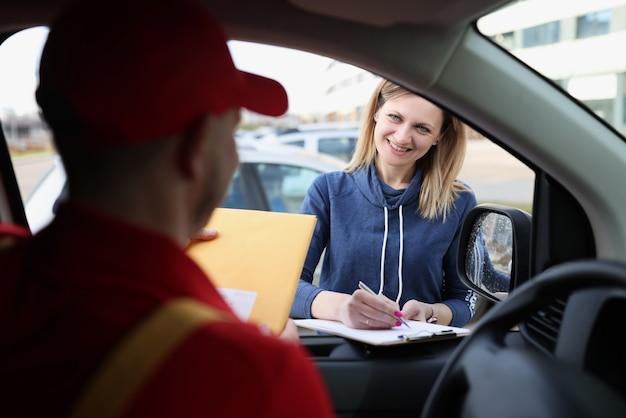 Kobieta stojąca w pobliżu samochodu z kurierem i podpisująca pokwitowanie dostawy