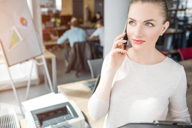 Kobieta stojąca w pokoju biurowym i rozmawia przez telefon