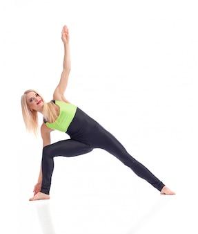 Kobieta stojąca w pozycji jogi na białym tle