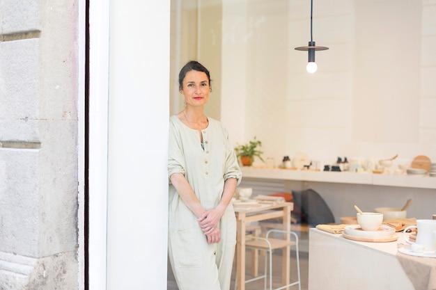 Kobieta stojąca w stroju roboczym w swoim warsztacie obok okna