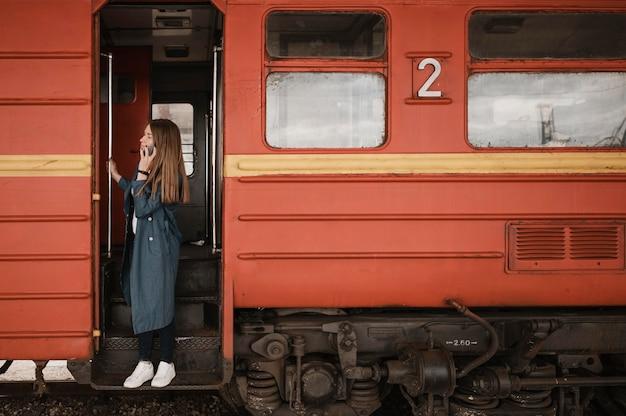 Kobieta stojąca w wejściu do pociągu i szukająca kogoś