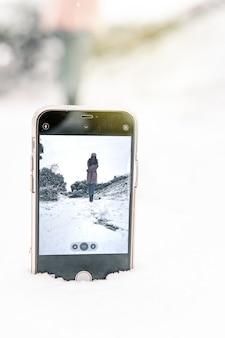 Kobieta stojąca w zimowym lesie i biorąc selfie smartfona umieszczonego w zaspie