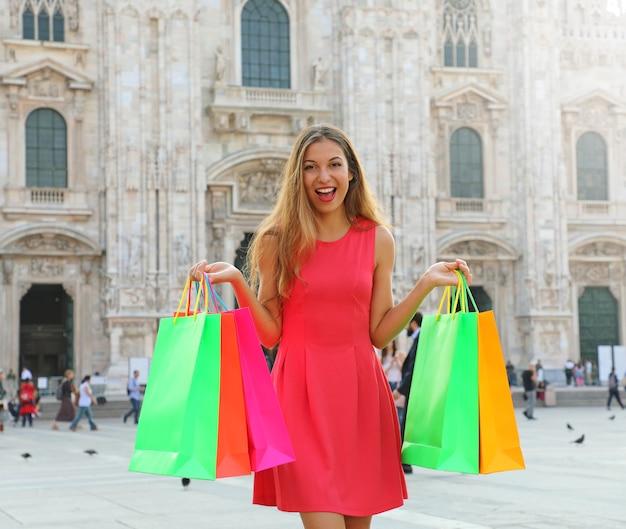 Kobieta stojąca z kolorowych toreb na zakupy w mediolanie we włoszech