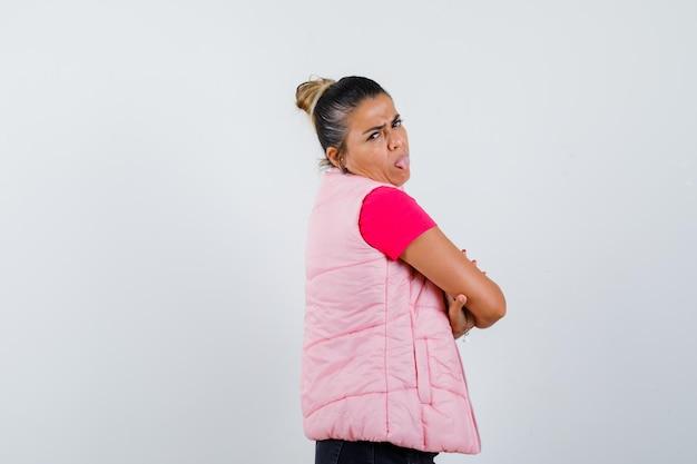 Kobieta stojąca ze skrzyżowanymi ramionami, wystająca język w koszulce, kamizelce i wyglądająca ponuro