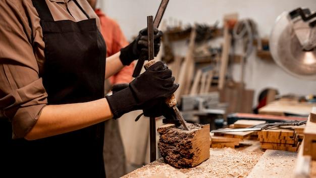 Kobieta stolarz rzeźbiący drewno w studio