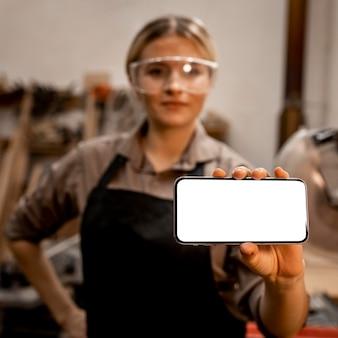 Kobieta stolarz trzymając smartfon w okularach