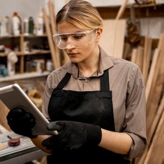 Kobieta stolarz trzymając tablet w okularach ochronnych