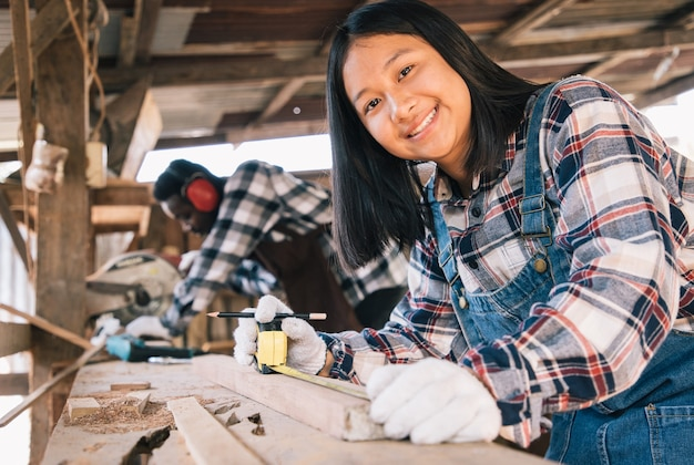Kobieta stolarz używa narzędzi do drewna z własnego mieszkania z asystentem w miejscu pracy