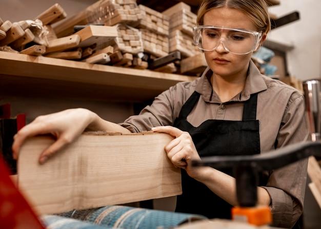 Kobieta stolarz z kawałkiem drewna w pracy