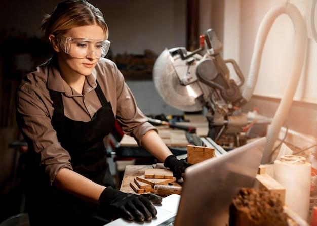 Kobieta stolarz z okularami ochronnymi za pomocą laptopa
