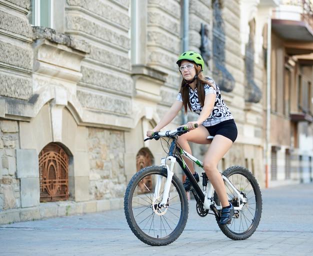 Kobieta stonowana rowerzysta jazda rowerem po brukowanych ulicach i pięknych starych budynków
