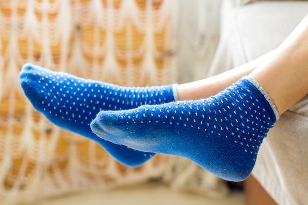 Kobieta stopy w niebieskich skarpetach. relaks i komfort wakacje koncepcja.