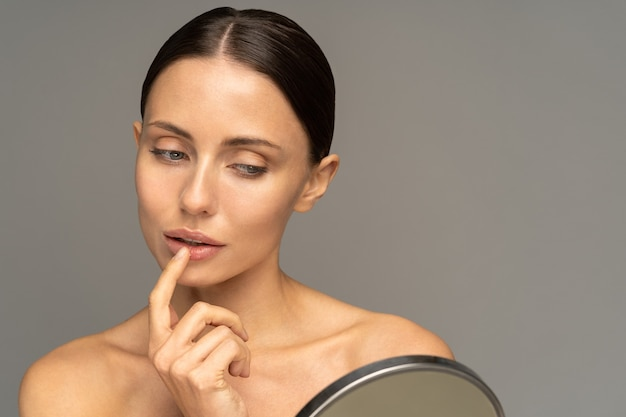 Kobieta stosowania balsamu do ust z palcem
