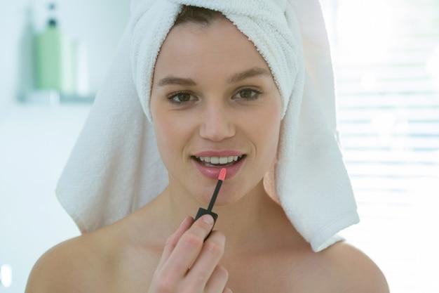 Kobieta stosowania błyszczyk na ustach w łazience