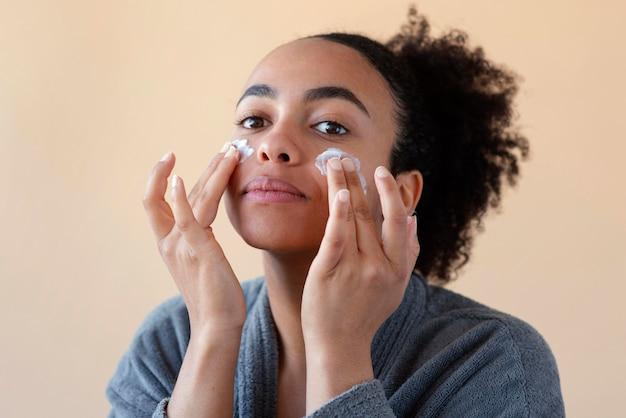 Kobieta stosowania kremu do twarzy z bliska