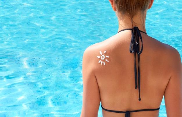 Kobieta stosując krem do opalania na ramieniu w postaci słońca. ochrona przed słońcem krem do opalania. pielęgnacja skóry i ciała. dziewczyna za pomocą kremu przeciwsłonecznego do skóry.