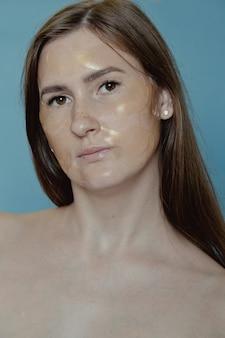 Kobieta stosująca plastry pod oczy, maskę na cienie i obrzęki. ładna dziewczyna nakłada złote płatki kolagenowe pod oczy. zabieg na twarz kobiety. kosmetologia, uroda i spa