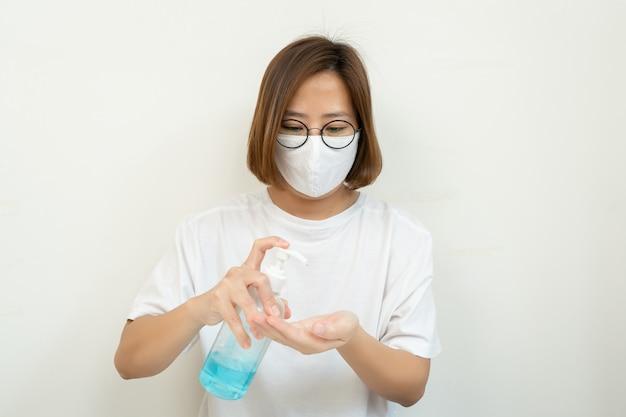 Kobieta stosująca produkt alkoholowy dezynfekujący w aerozolu pod ręką, myjąca dłoń środkiem dezynfekującym alkohol, zapobiega wirusowi i bakteriom