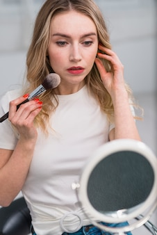 Kobieta stosuje blusher patrzeje w lustrze