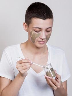 Kobieta stosuje borowinowego traktowanie na twarzy