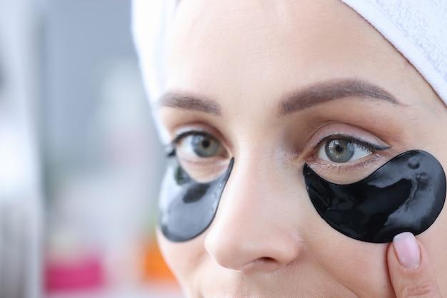 Kobieta stosuje czarne łaty pod oczami, aby zlikwidować obrzęki i wygładzić zmarszczki
