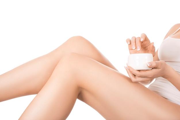 Kobieta stosuje śmietankę na ona nogi na biel ścianie. koncepcja pielęgnacji i zdrowia skóry.