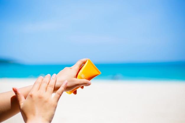 Kobieta stosuje sunscreen ochrony śmietankę przeciw turkusowemu morzu karaibskiemu