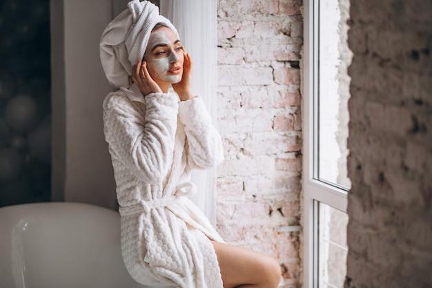 Kobieta stosuje twarzowego maskin łazienkę