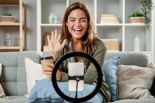 Kobieta streaming na żywo podczas picia kawy
