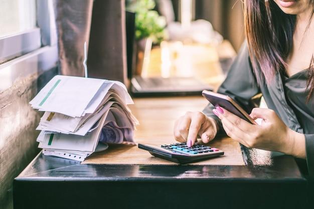 Kobieta strony obliczania długu z inteligentny telefon