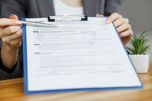Kobieta strony pisania lub podpisywania w dokumencie