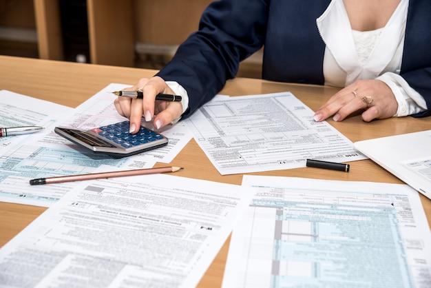Kobieta strony wypełniania formularzy podatku dochodowego z kalkulatorem