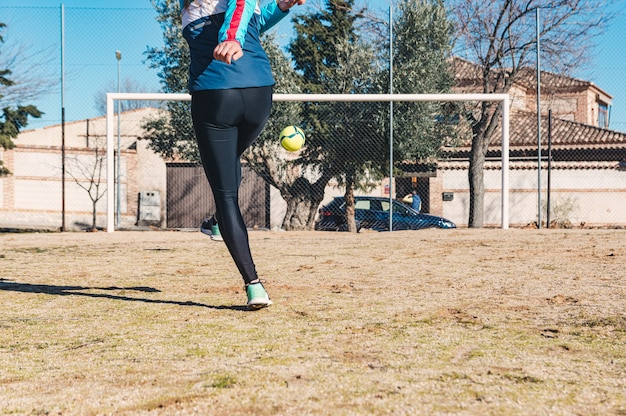 Kobieta strzela z rzutu wolnego w kierunku bramki. boisko do piłki nożnej. koncepcja kobiecej piłki nożnej.
