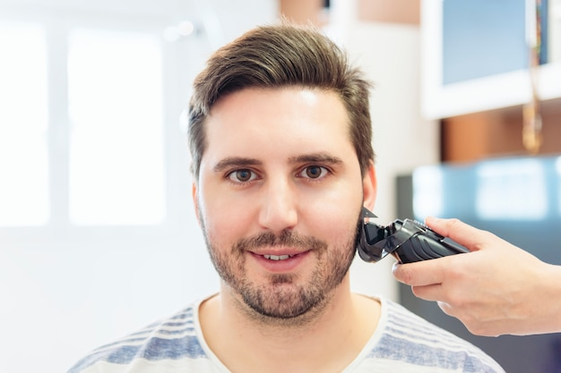 Kobieta strzyżenia włosów młodego mężczyzny w prowizorycznym salonie fryzjerskim w domu