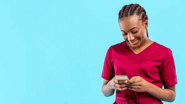 Kobieta student medycyny patrzeje jej telefon