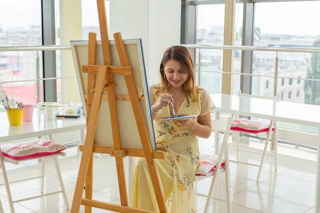 Kobieta student siedzi przed sztalugą z paletą