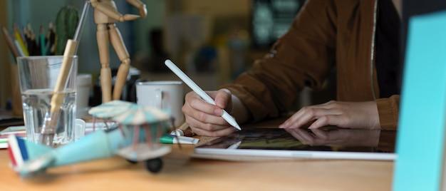 Kobieta studentka robi zadanie z cyfrowego tabletu, książek i materiałów eksploatacyjnych na drewnianym stole