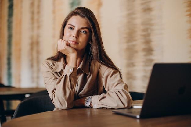Kobieta studentka studiuje na laptopie w kawiarni