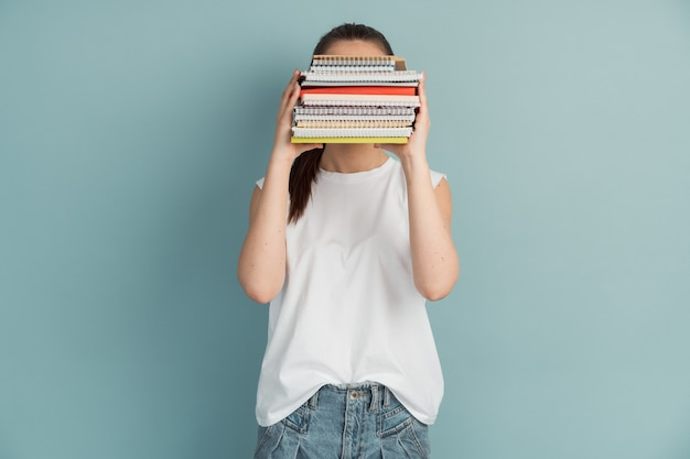 Kobieta studentka z góry zeszytów i książek w dłoniach