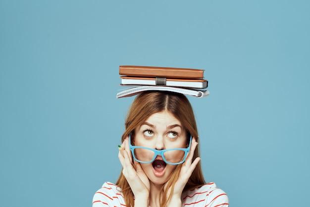 Kobieta studentka z książkami na głowie nauka edukacja niebieskie tło emocje gestykuluje rękami.