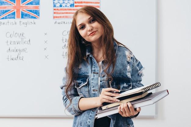 Kobieta studentka z książkami w klasie szkoły języka angielskiego.
