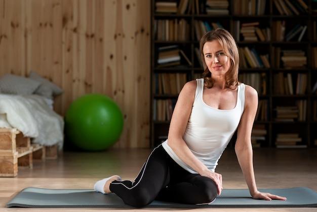 Kobieta stwarzających na matę do jogi
