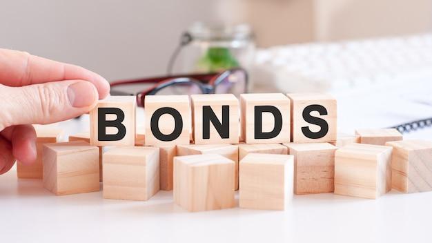 Kobieta stworzyła słowo obligacje z drewnianymi klockami, koncepcja biznesowa selektywna ostrość