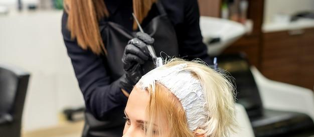 Kobieta stylistka włosów nakłada biały barwnik na włosy młodej klientki w salonie fryzjerskim